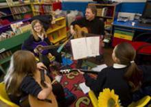 Three school girls practising guitar