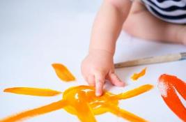 Baby crawls floor playing with paints