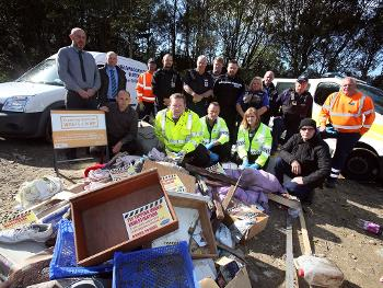 A group of people next to a pile of flytipping
