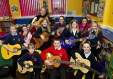 School children playing guitar